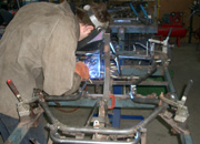 Mark makes repairs to a kart frame